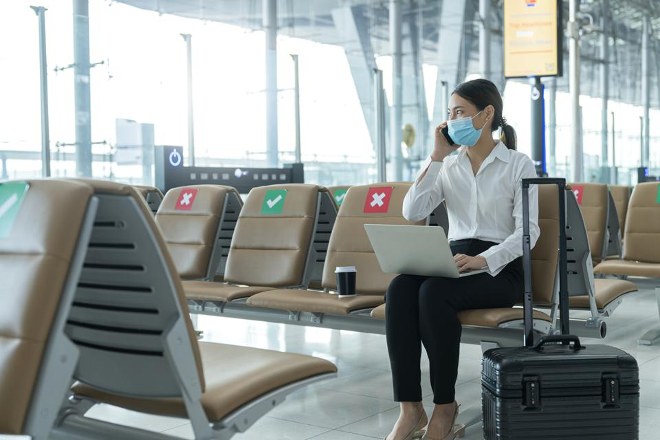 Social distancing, businesswoman wearing face mask sit working with laptop keeping distance away from each other to avoid covid19 infection during pandemic. Empty chair seat red cross shows new normal