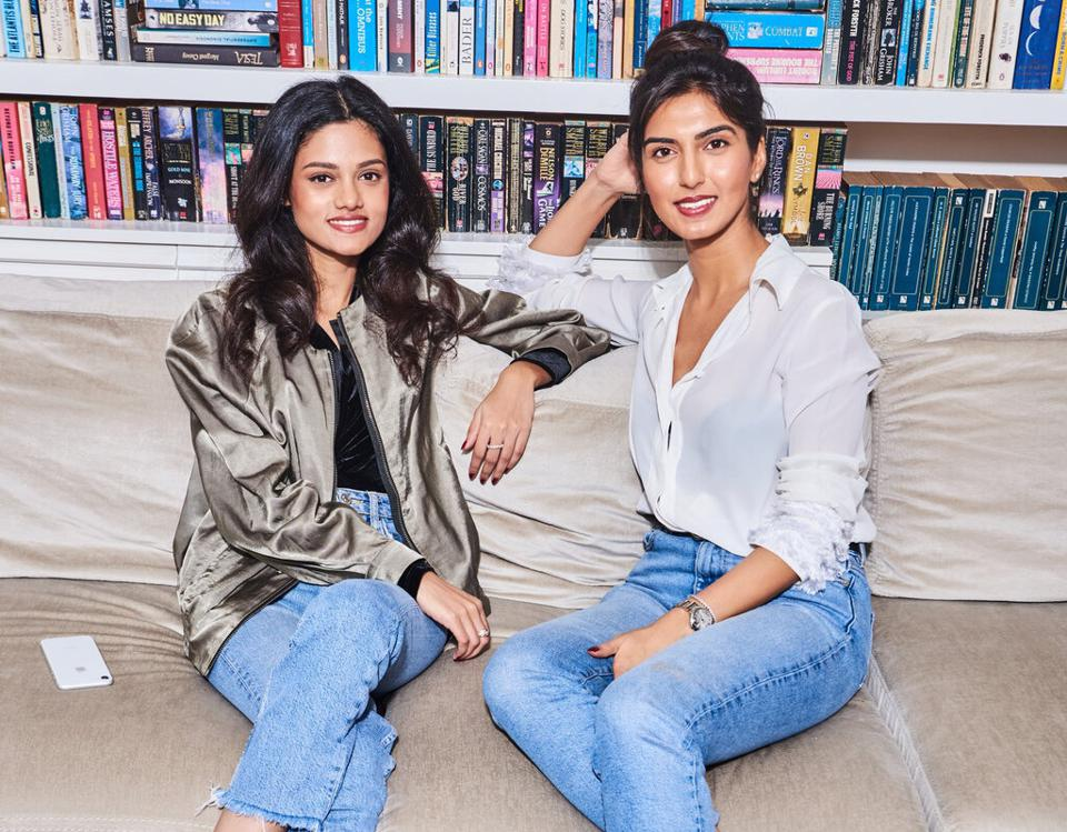 Volv co-founders Shannon Almeida and Priyanka Vazirani seated in front of books