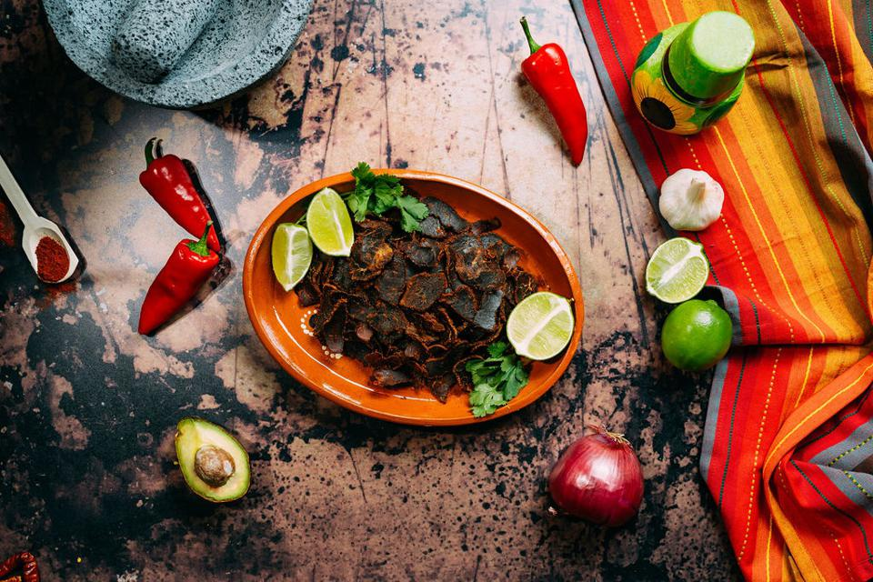 carne seca on a plate surrounded by limes and chili peppers
