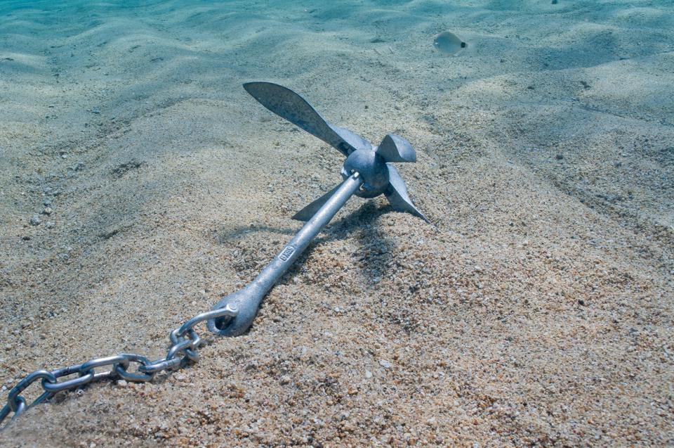 An anchor underwater on a sandy seafloor.
