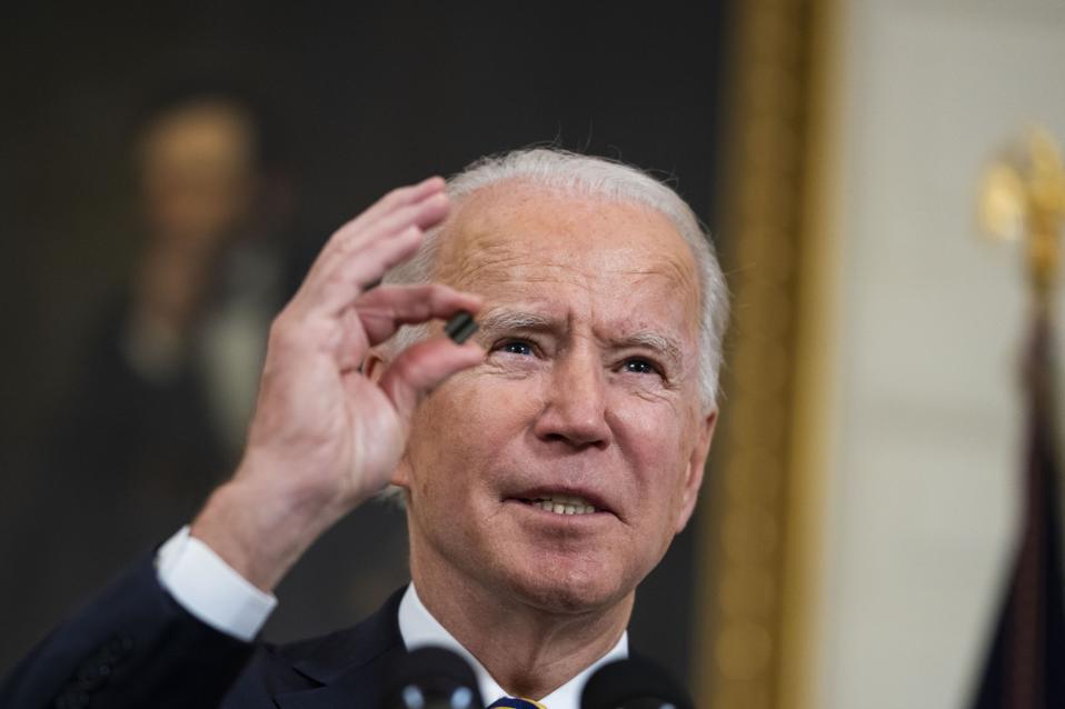 President Joe Biden holds up a semiconductor