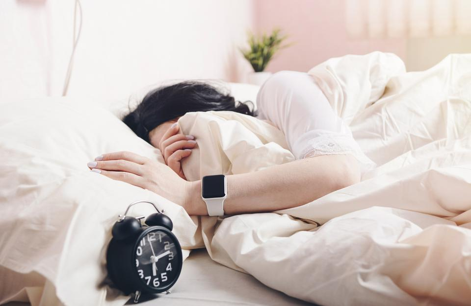 Woman Sleeping By Alarm Clock On Bed