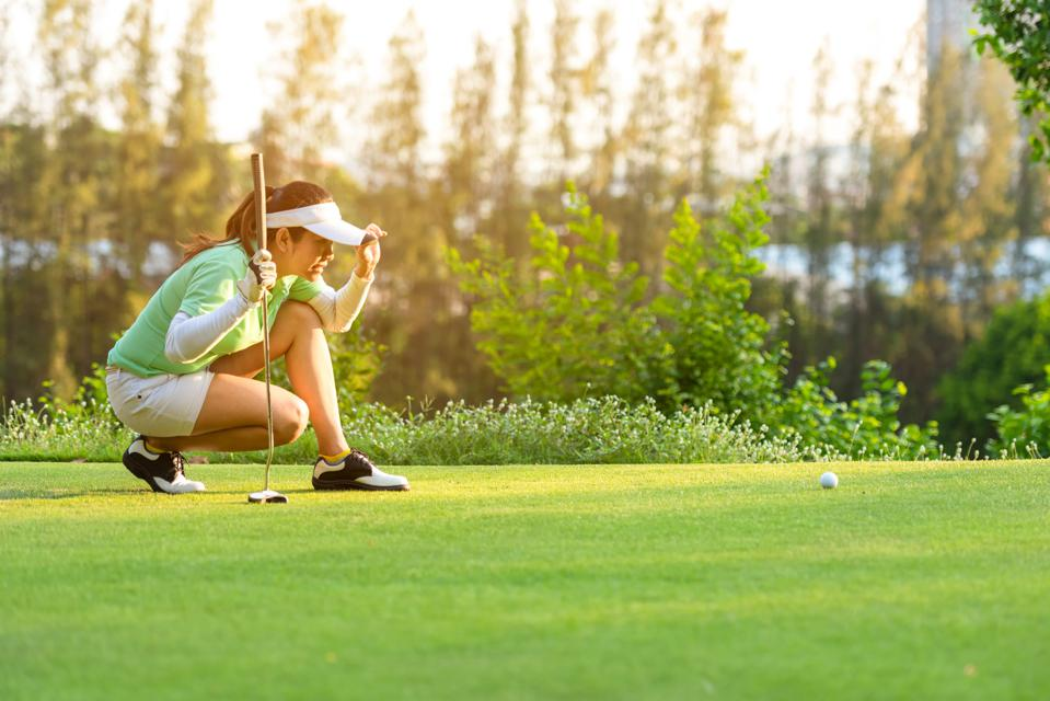 Sporty asian woman golf player crouching and study the green before putting shot in vacation and holiday.  Sport and Healthy Concept