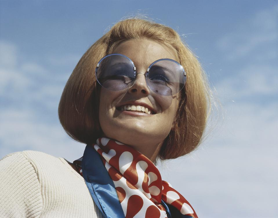 Young woman wearing sunglasses, smiling, close-up