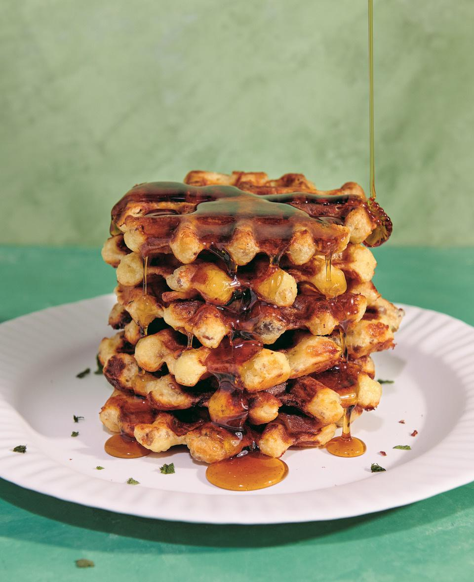 A crispy stack of Cheesy Sausage and Sage Waffles is being drizzled with maple syrup on a white plate. The recipe is from the new cookbook ″It's Always Freezer Season,″ by Ashley Christensen and Kaitlyn Goalen.