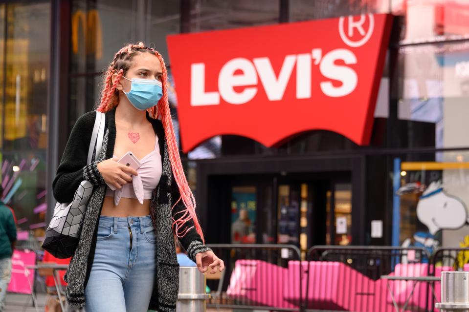 Masked consumer walks by Levi's store in Manhattan.