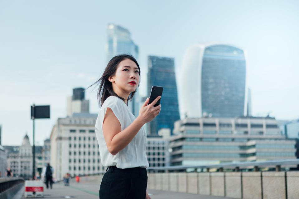 Businesswoman using smartphone in financial district
