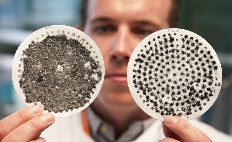 A white man holds up two round filters. One is covered in gray gunk, the other has less.