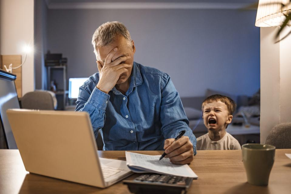 Stressed Man With his two years old son Working From Home