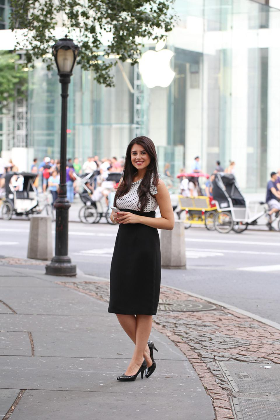 Woman standing on the street in New York City in front of an Apple Store.