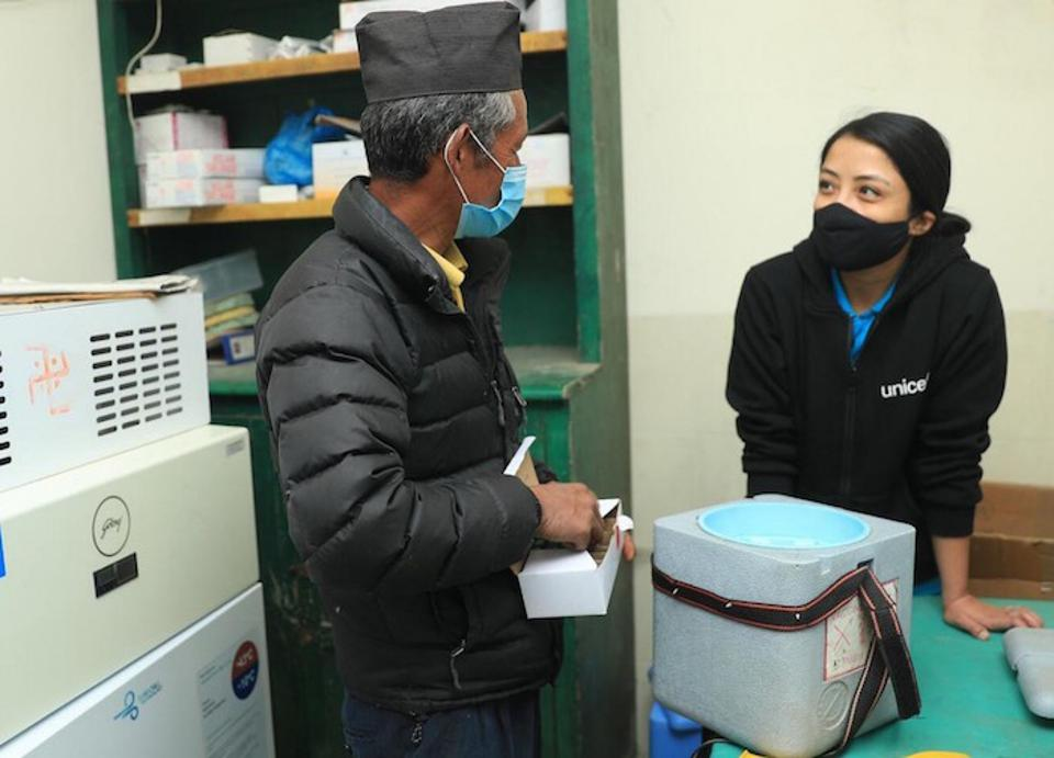 Mitthi Bahadur Jirel (left), a 29-year staff veteran at Jiri district hospital in northeastern Nepal's Dolakha district, shows UNICEF Nepal Communication Officer Preena Shrestha an insulated vaccine carrier in the hospital's vaccine storage room.