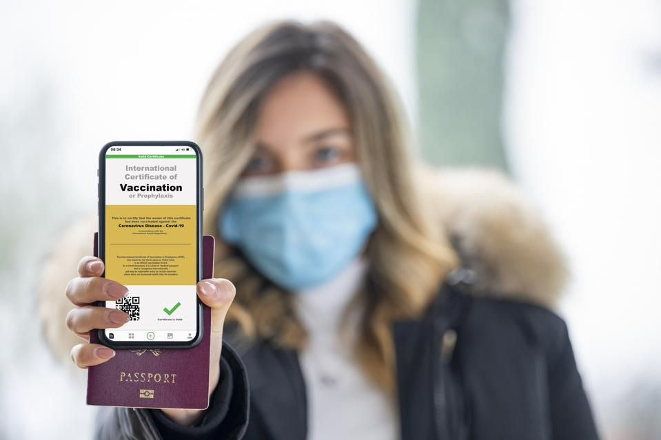 A defocused young girl, wearing a face mask, is holding a passport and a smart phone with a with an example of a certificate of vaccination against the Covid-19 disease.