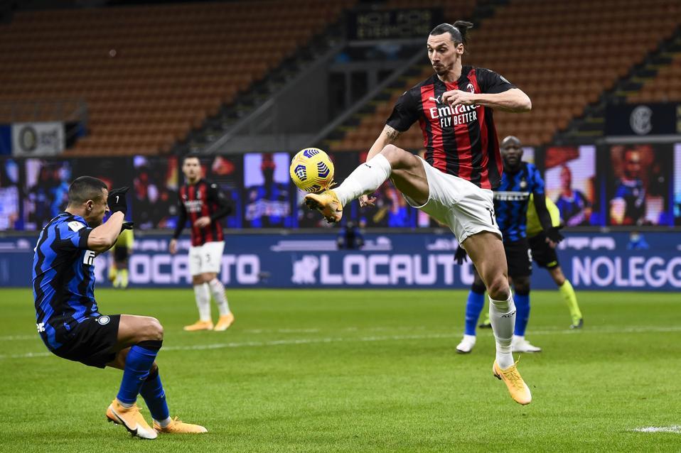 Zlatan Ibrahimovic (R) of AC Milan controls the ball during...