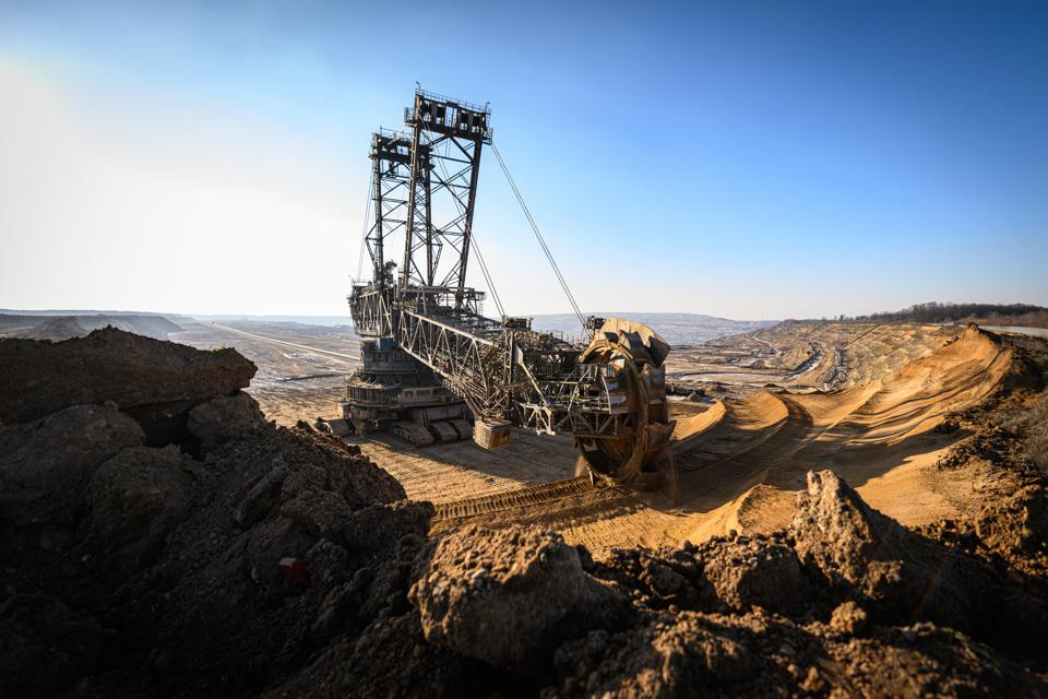 A vast excavating machine mines lignite coal under a blue sky in Germany.