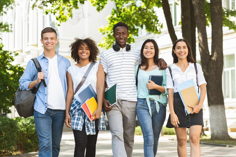 Cheerful college students walking out of campus together, posing outdoors