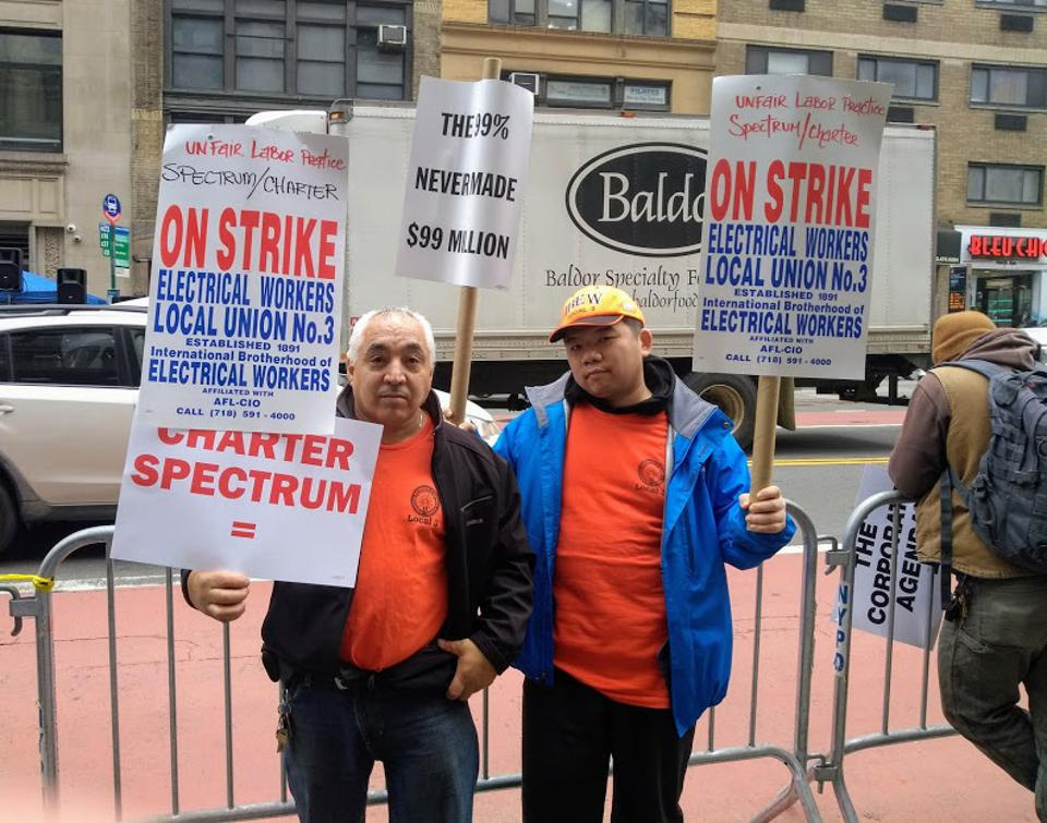 Two cable technicians hold Charter-Spectrum strike signs on 23rd Street in New York City.