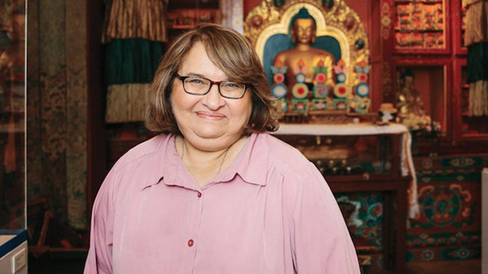 Photo of Sharon Salzberg smiling inside of a Buddhist Temple