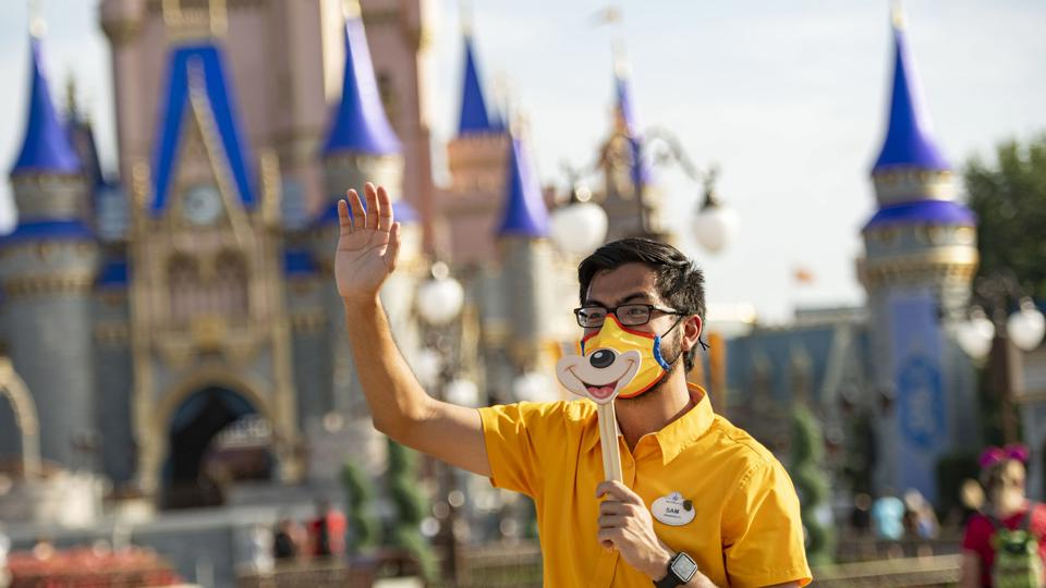 Walt Disney World cast member waves to guests in front of castle