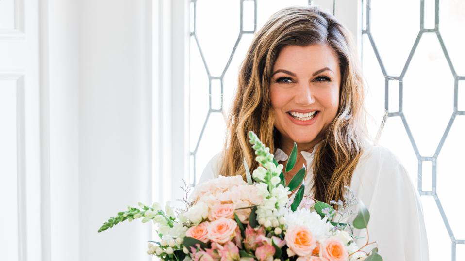Tiffani Thiessen smiling at the camera and holding flowers