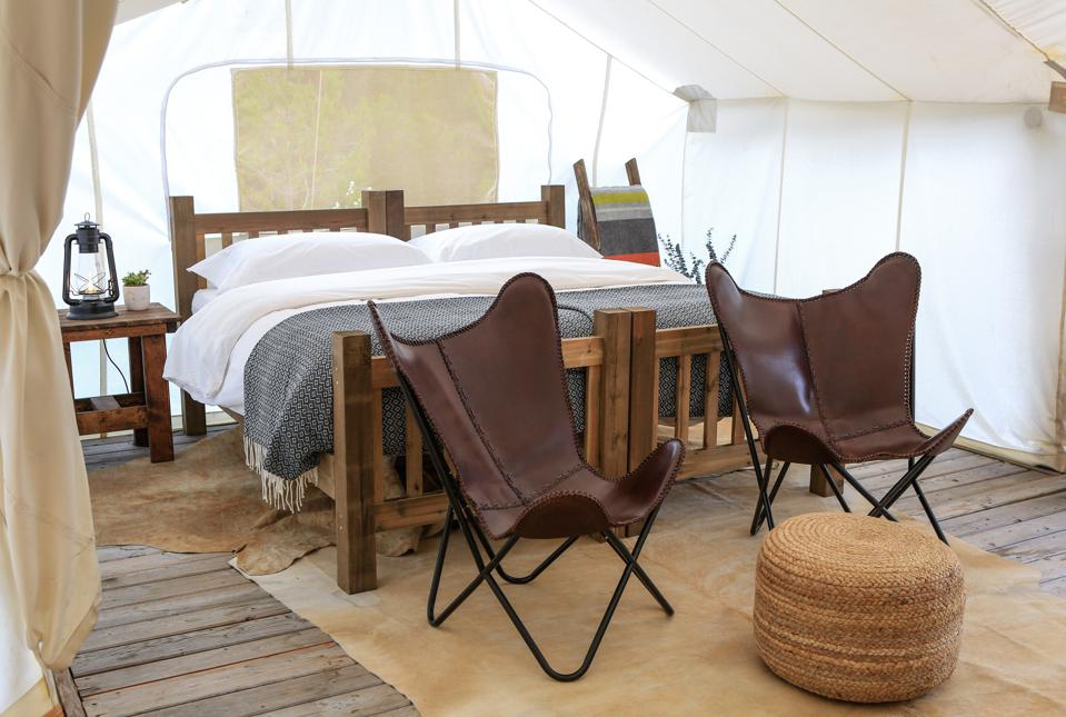 A king sized bed and two leather chairs within a tent