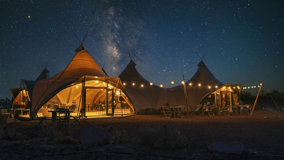 A large combined tent at night under starry skies