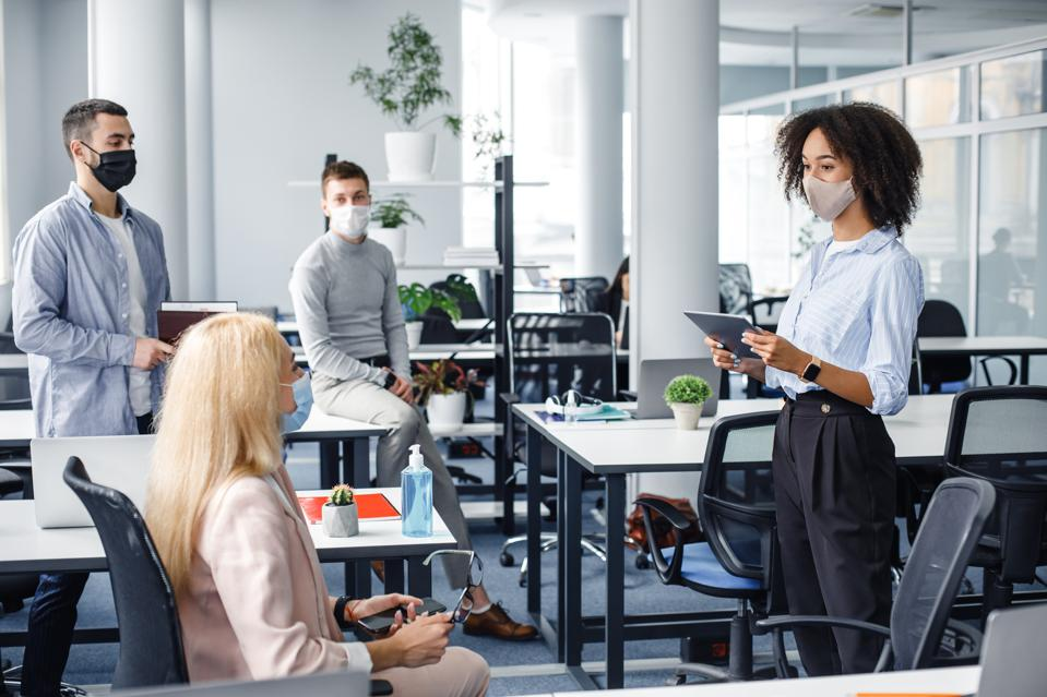 Office workers talk with masks on at a distance from one another.