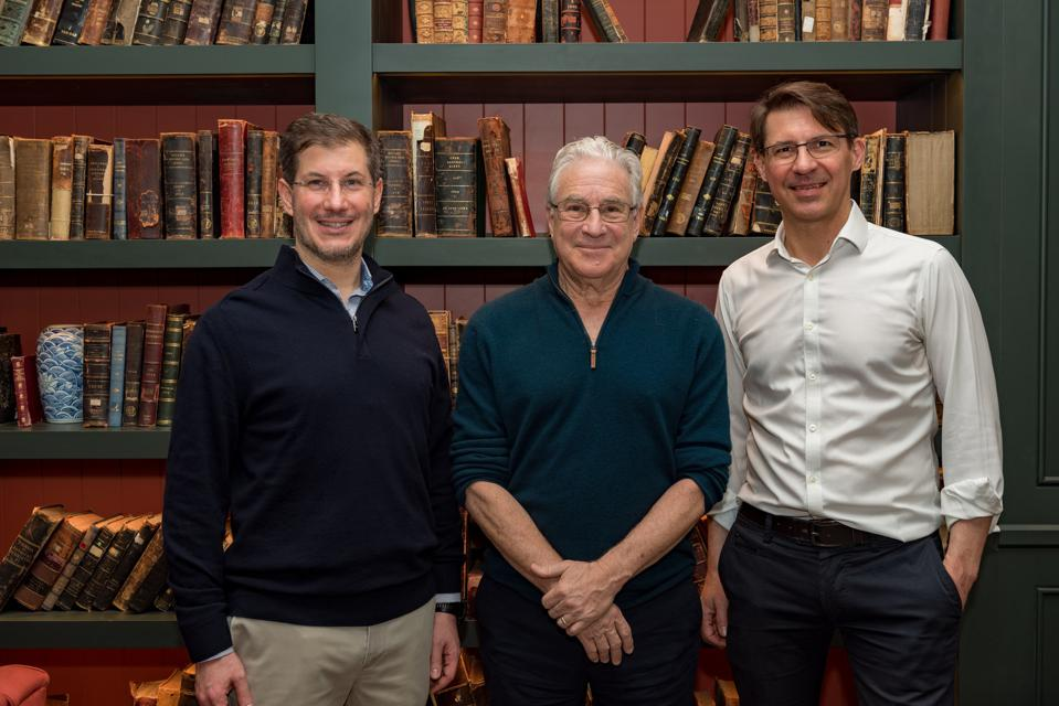 Three men standing in front of antique books smiling at camera