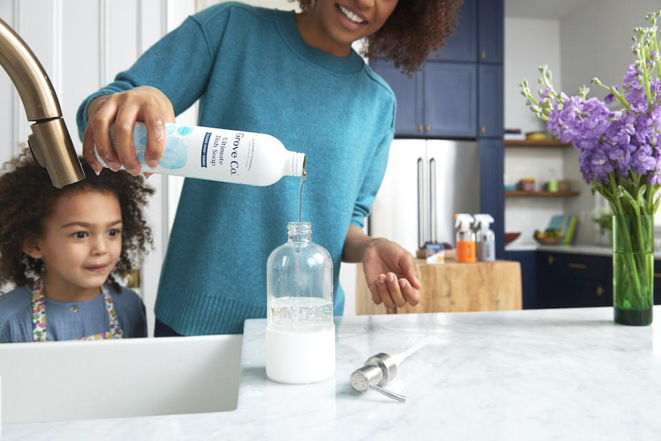 Grove liquid soap refilled by a woman and a child