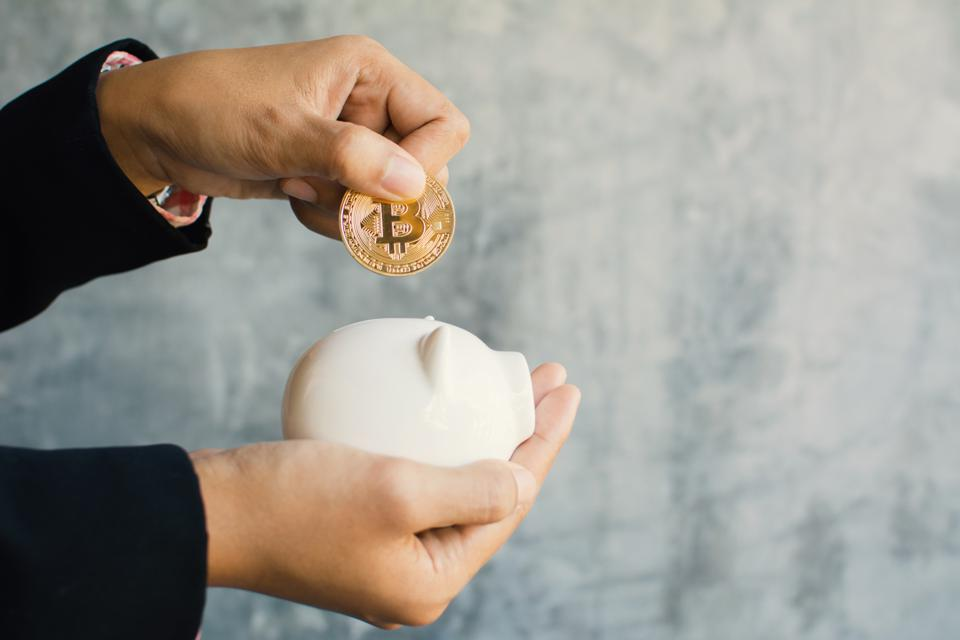 Cropped Hands Putting Bitcoin In Piggybank Against Wall
