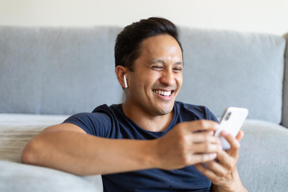 Man smiling during a video call on his cell phone at home