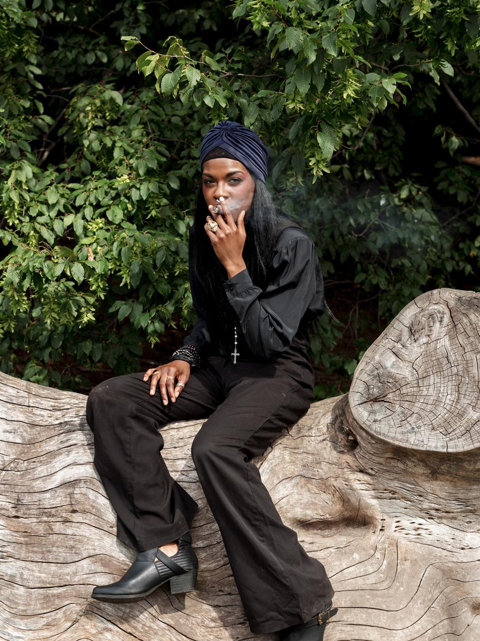 A witch dressed all in black, smoking a cigarette
