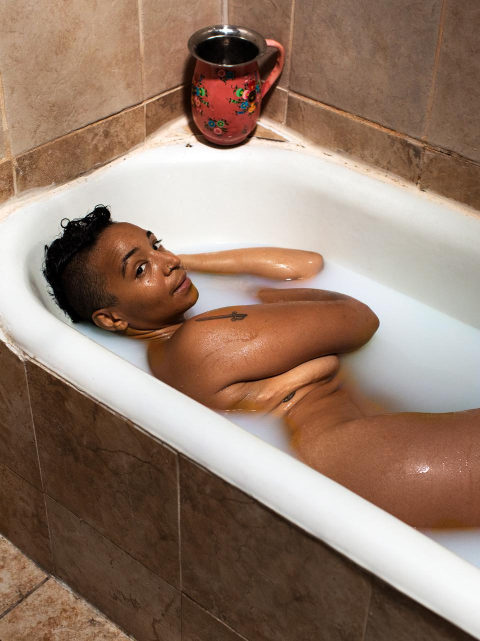 A black witch naked, lying in a bathtub, looking back over her shoulder at the camera.