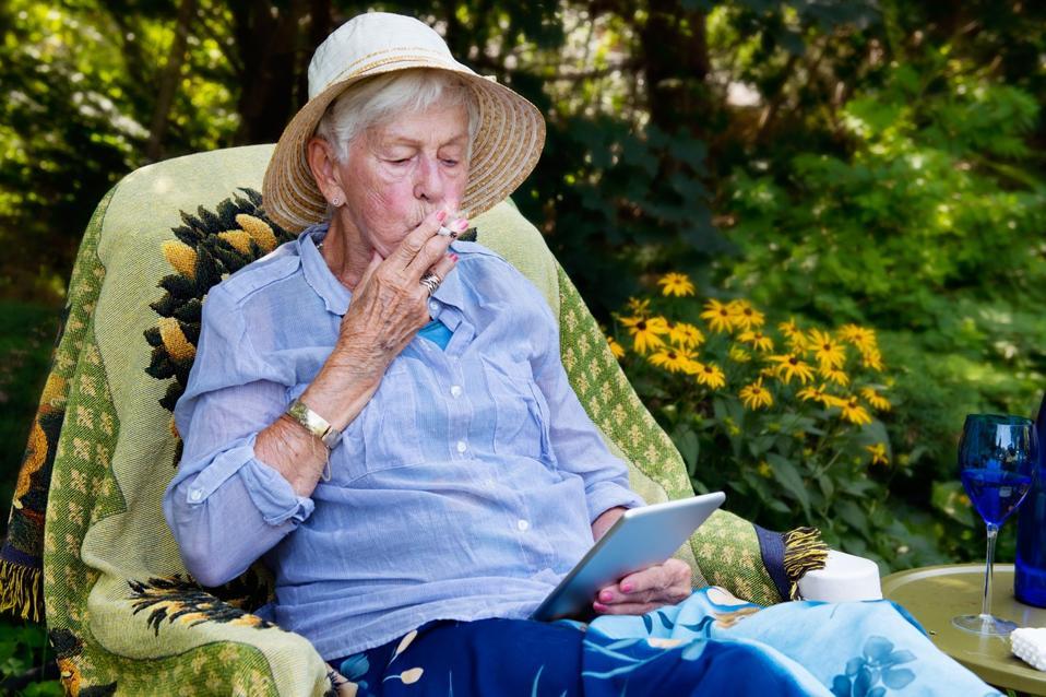 Happy senior woman smoking marijuana joint as cannabis medicinal