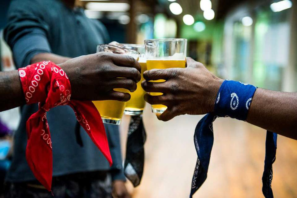 Three Black men toast with beers while wearing bandanas around their arms with colors that show their rival gang affiliations