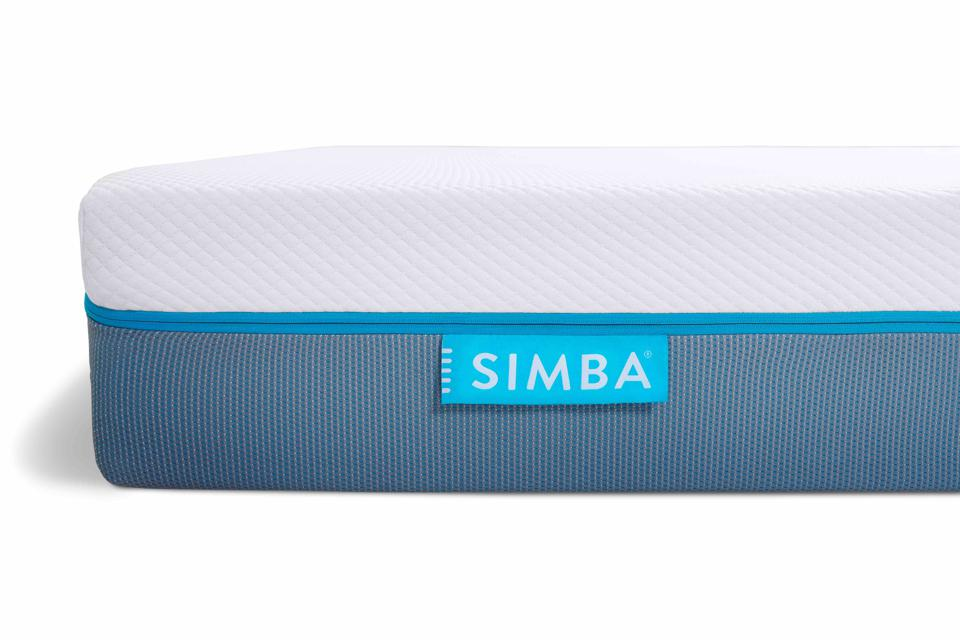 A layered mattress with blue stitching and a grey underside
