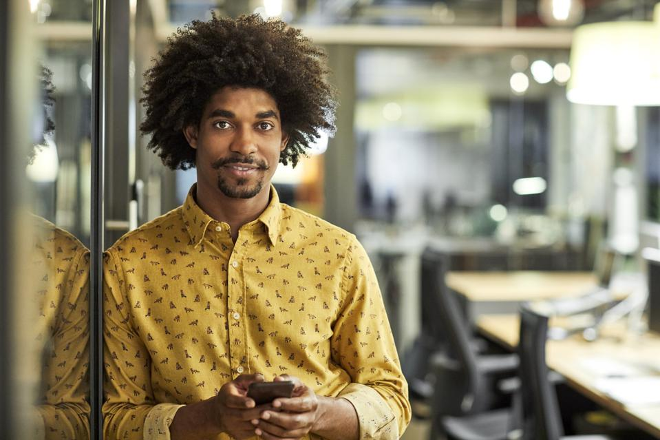 Confident businessman with mobile phone in office