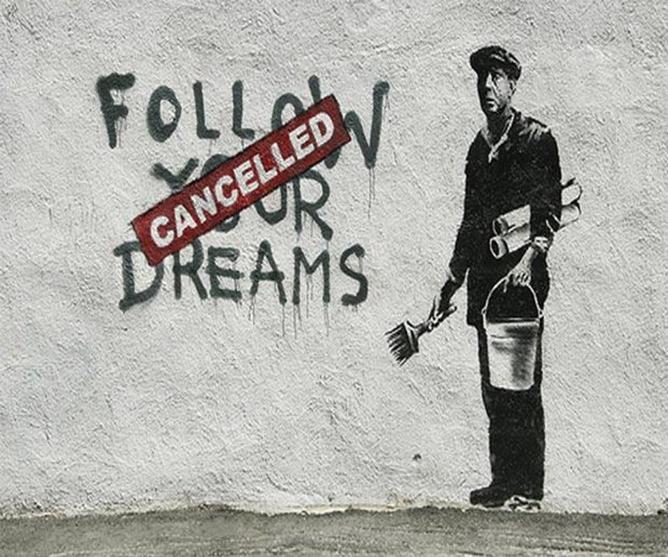 Man holding paintbrush by wall that reads ″follow your dreams″ with ″cancelled″ banner.