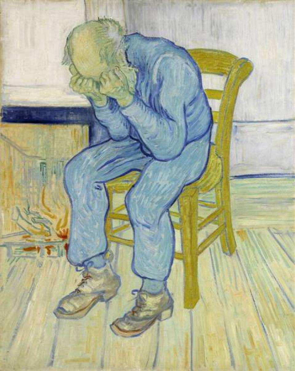A depressed man sits in a wooden chair, with his hea din his hands