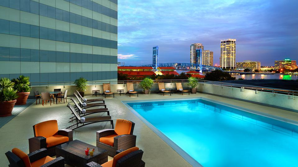 An outdoor pool surrounded by chairs, with a city skyline in the background