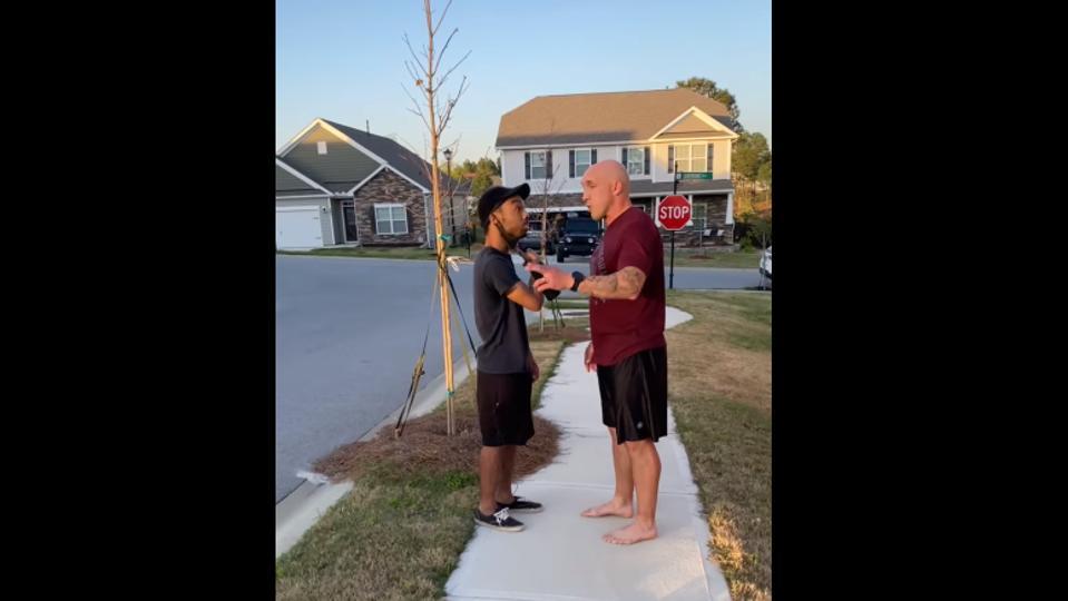 Jonathan Pentland confronts a black man on a sidewalk outside a home.