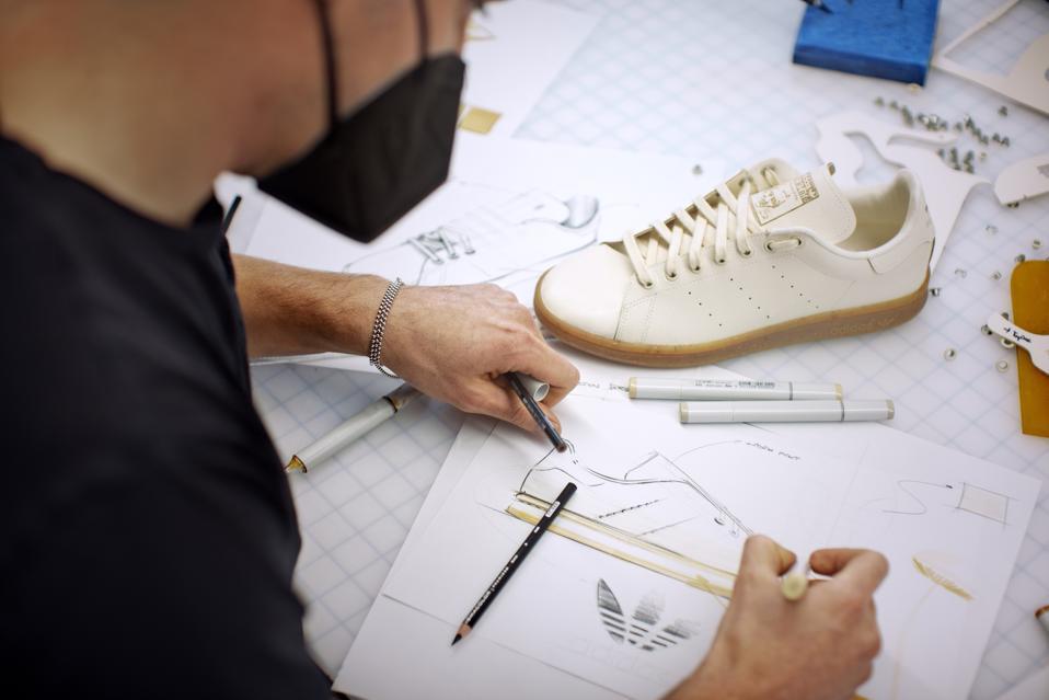 A man draws shoe designs next to the white Mylo Adidas Stan Smith shoe.