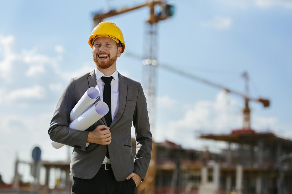 Architect with blueprints on construction site