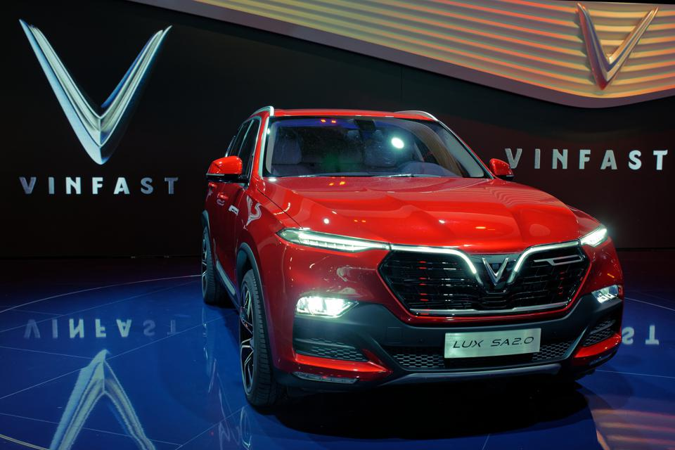 Red VinFast Lux SA 2.0 SUV at the Paris Motor Show in 2018, with the VinFast logo in the background.