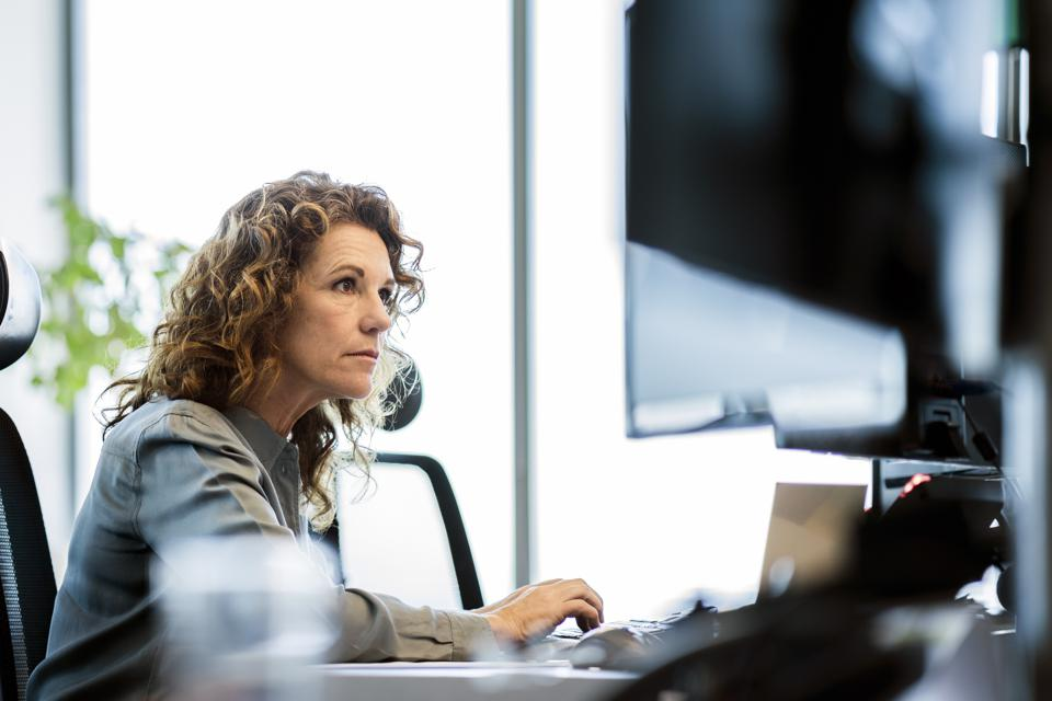 Serious businesswoman using computer at desk