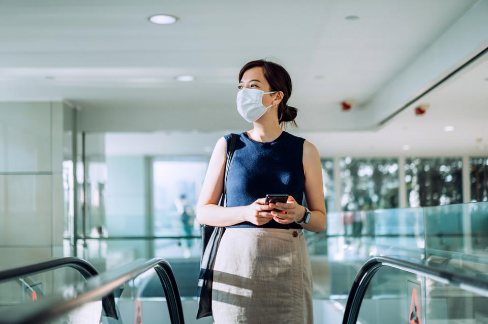 Professional young Asian businesswoman with protective face mask commuting to work in the morning, holding smartphone on hand while riding on the escalator in an office building