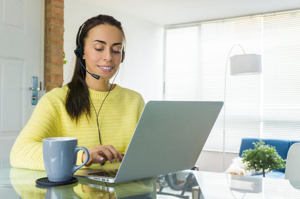 Woman working online at home and using headset on a video conference