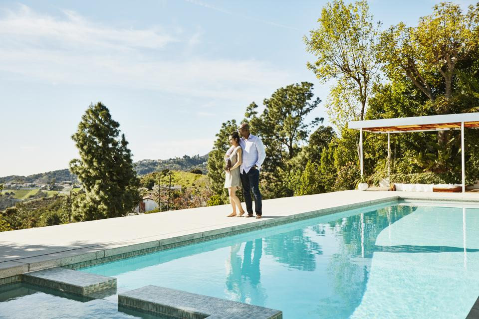 Embracing couple standing next to pool and admiring view