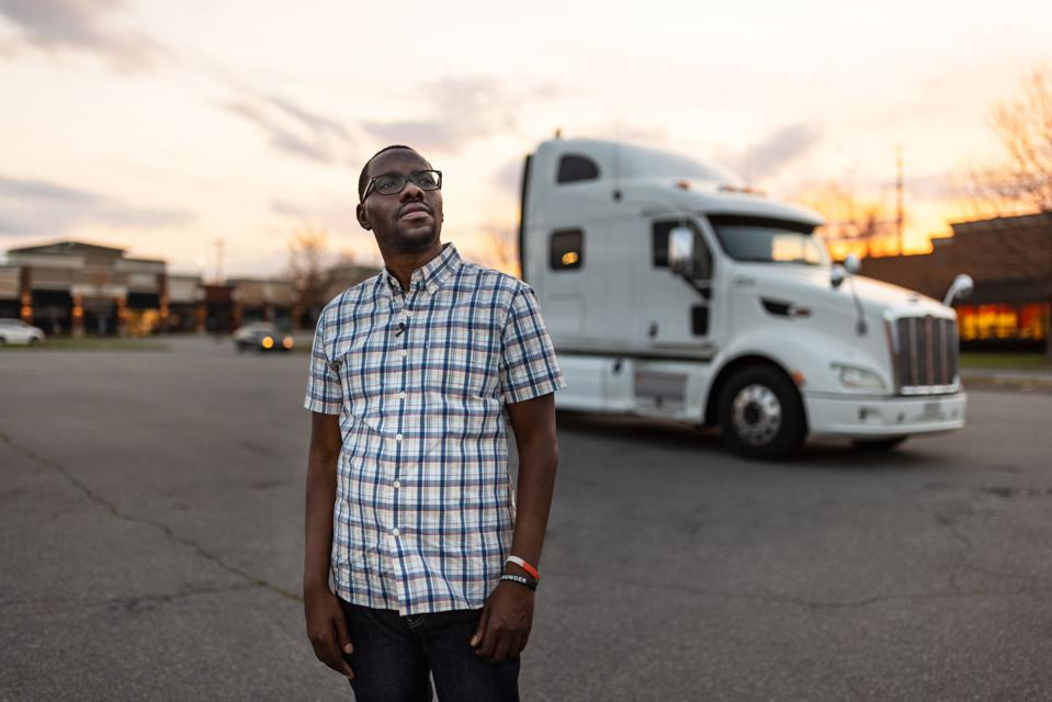 man standing in front of big rig truck