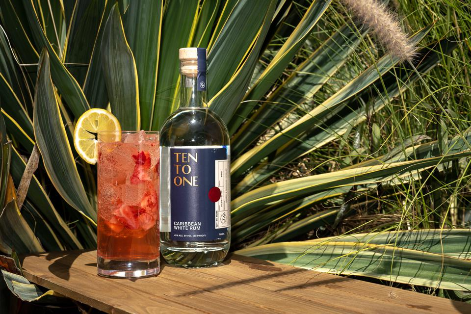 A red cocktail and a bottle of rum with a lush tropical background