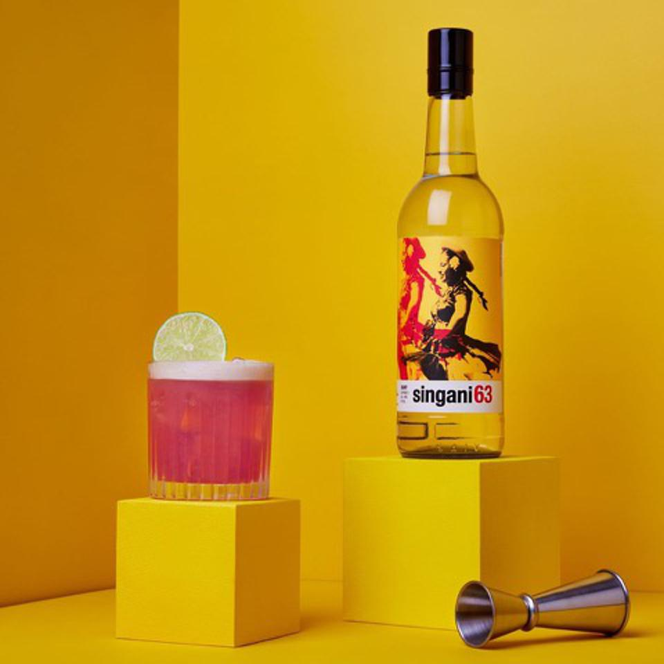 a pink cocktail on a yellow background